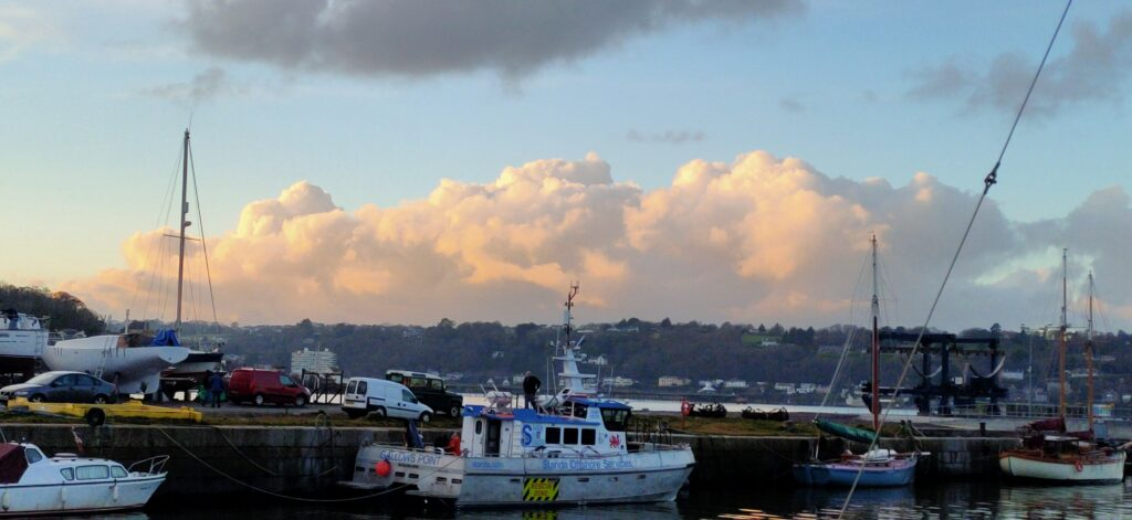 Clouds beyond the harbour wall