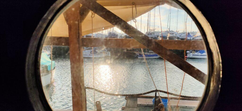 View of a shipyard through a porthole
