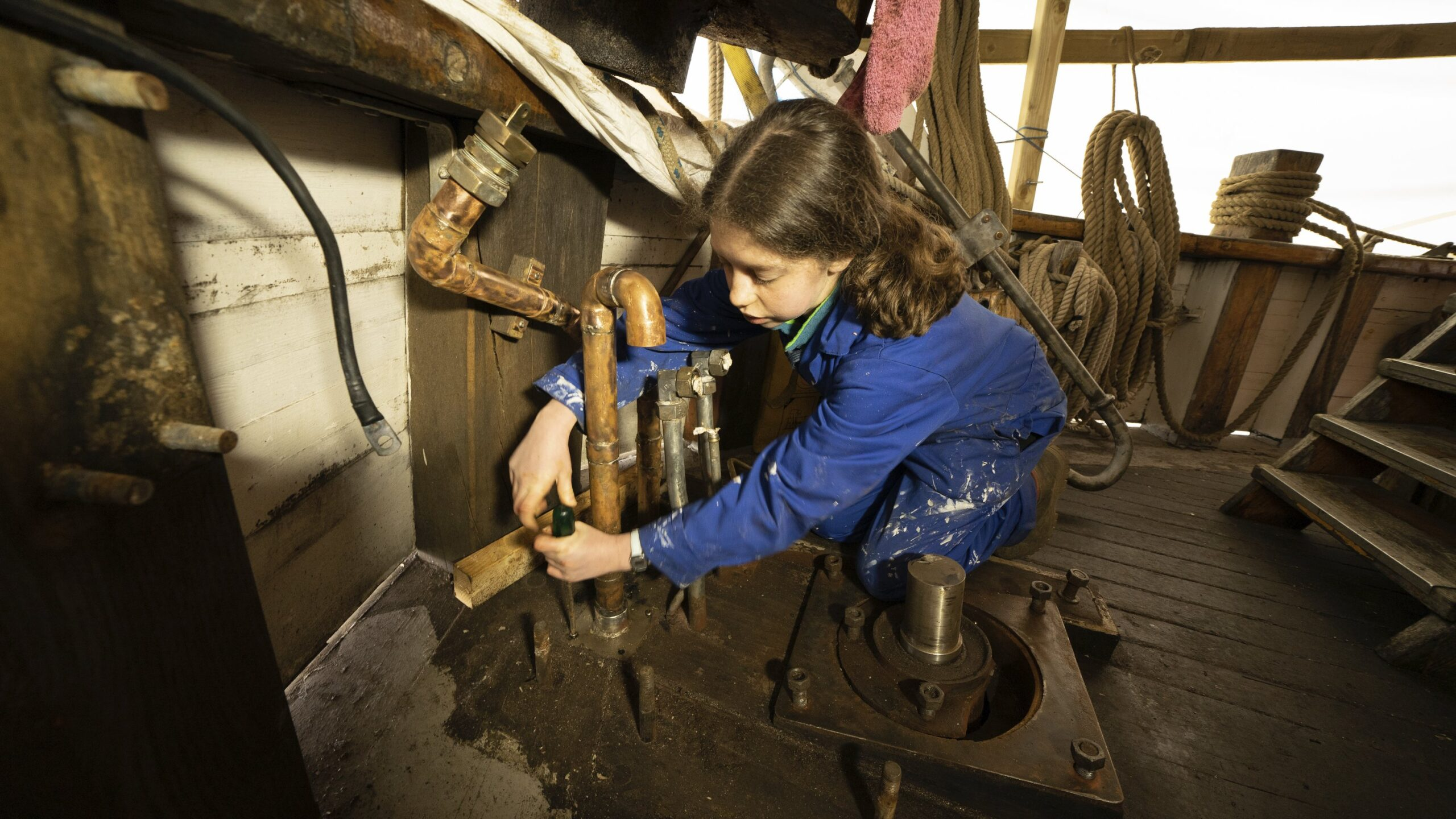 Girl with screwdriver and pipework