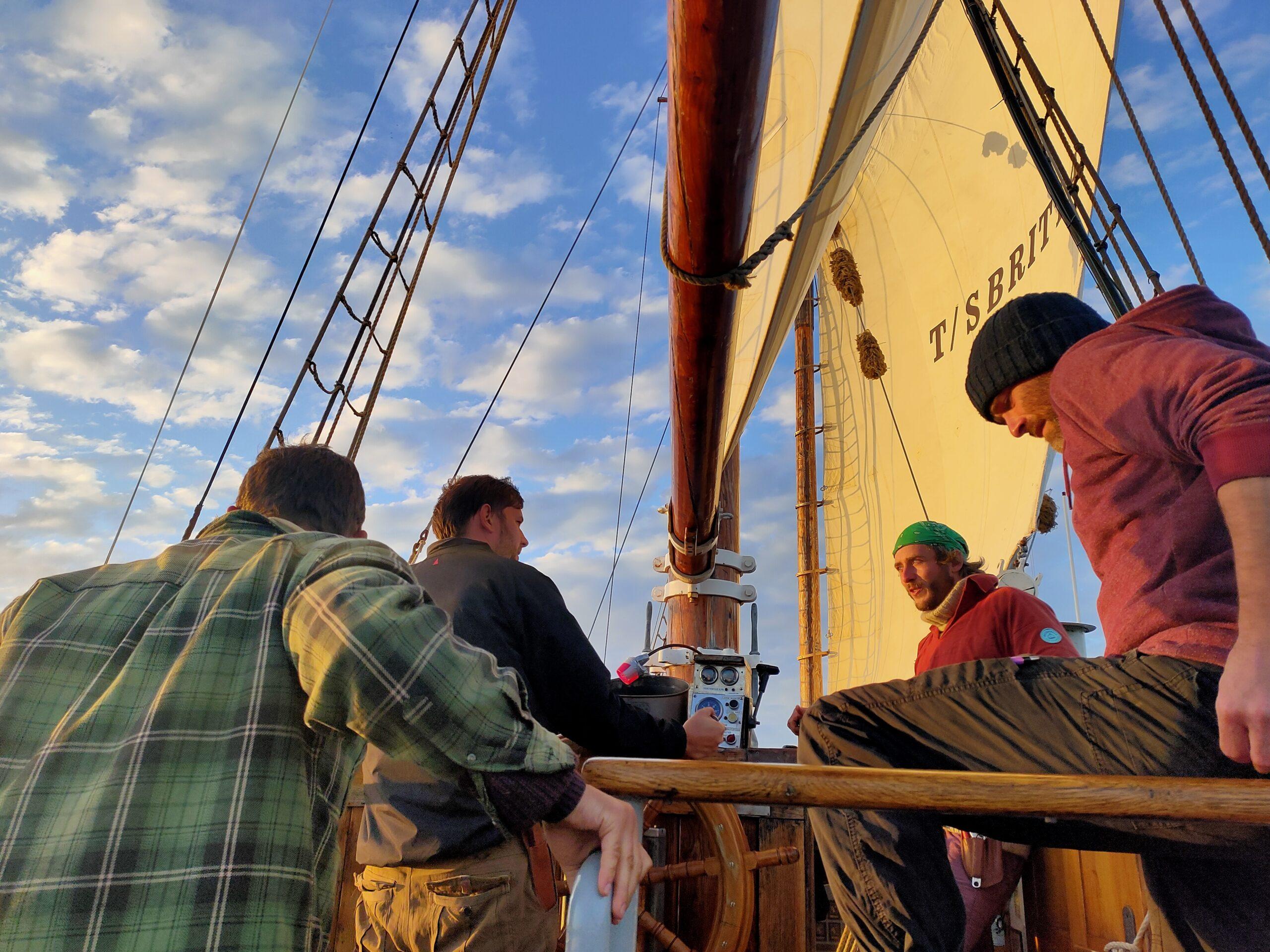 Three crew talking to skipper of sailing ship